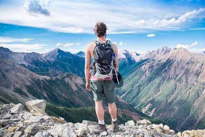 Man med ryggsäck tittar ut över bergig vy