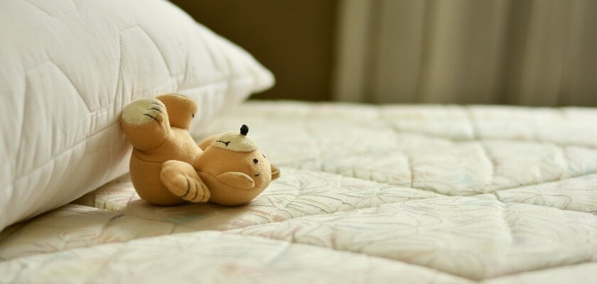 En liten nalle på en säng